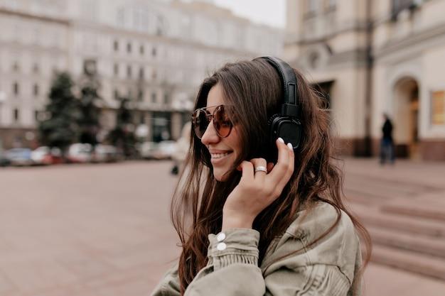 Emocionada niña feliz con cabello oscuro con chaqueta caqui y elegantes gafas escuchando música con auriculares y disfrutando de caminar por la calle en la ciudad vieja