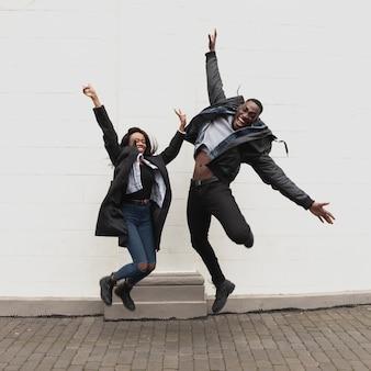 Emocionada pareja afroamericana saltando tiro completo
