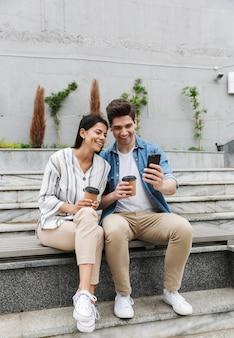 Emocionada pareja hombre y mujer en ropa casual bebiendo café para llevar y usando el teléfono inteligente en las escaleras de la ciudad al aire libre