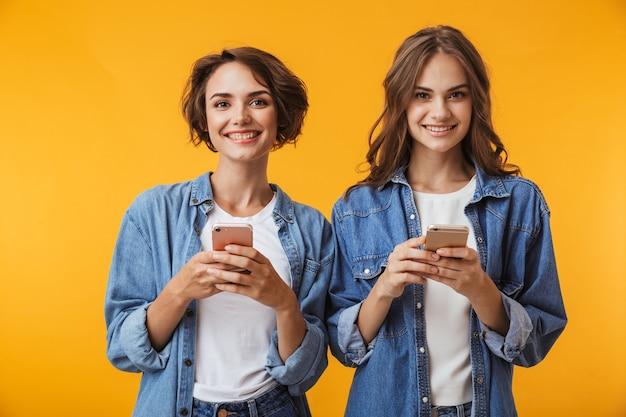 Emocionadas amigas jóvenes usando teléfonos móviles.