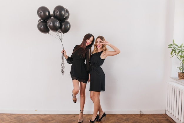 Emocionadas mujeres morenas en elegantes zapatos de tacón de pie sobre una pierna y sosteniendo globos