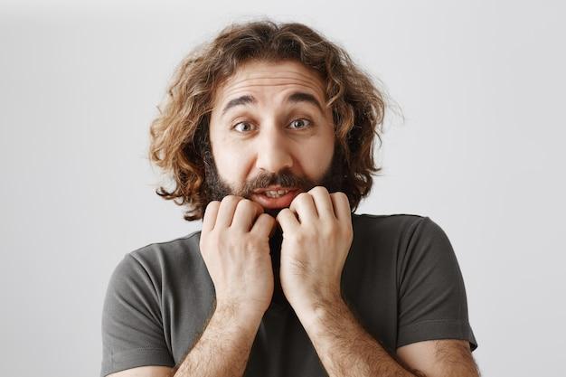 Emocionado y abrumado chico del medio oriente con las manos en la barbilla, esperando algo