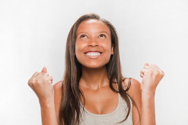 Emocionado adolescente africano mirando contra la superficie blanca