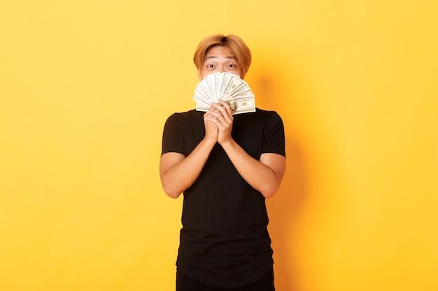 Emocionado chico asiático rubio afortunado regocijándose de ganar dinero en efectivo, sosteniendo dinero y luciendo feliz, de pie pared amarilla