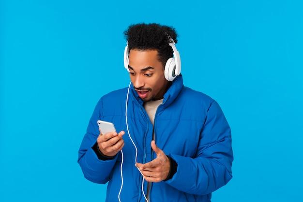 Emocionado y divertido, feliz y sonriente hombre afroamericano viendo al artista favorito subiendo una nueva canción, sosteniendo el teléfono presionando play como escuchando música en los auriculares de pie calle de invierno, pared azul