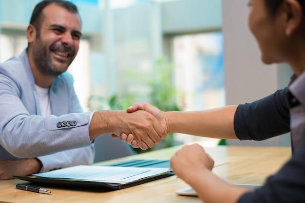 Emocionado empleador hispano felicitando a nuevo empleado.