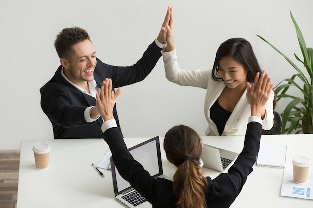 Emocionado equipo multirracial tomados de la mano dando alta celebrando el éxito cinco