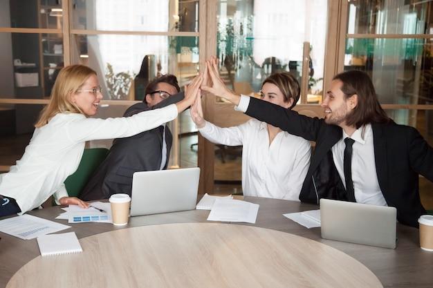 Emocionado equipo de trabajo dando alta cinco celebrando logros compartidos