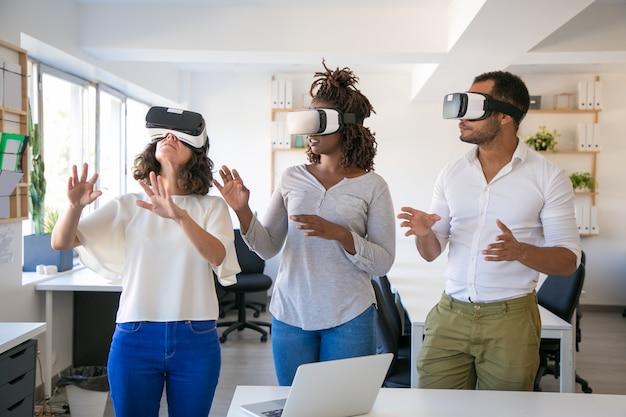 Emocionado equipo de tres simuladores de realidad virtual de prueba