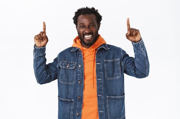 Emocionado, feliz guapo alegre barbudo afroamericano, de pie en chaqueta de mezclilla, sudadera con capucha naranja