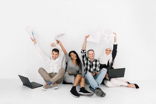 Emocionado grupo de cuatro amigos multiétnicos con las manos levantadas, sentados juntos en el suelo sobre fondo blanco.
