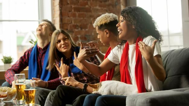 Emocionado grupo de personas viendo el campeonato de partidos deportivos en casa