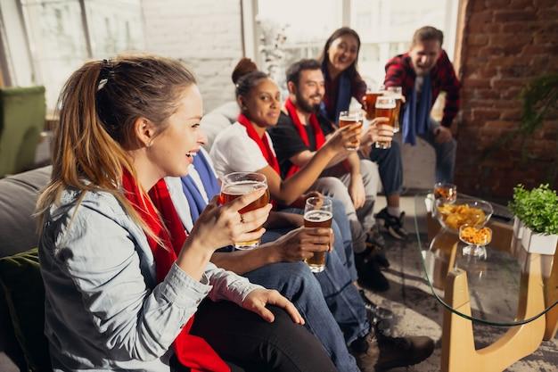 Emocionado grupo de personas viendo fútbol, partido deportivo en casa