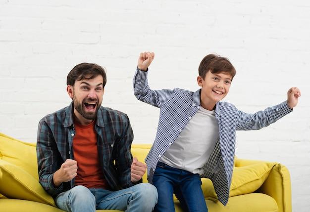 Emocionado hijo y padre sentado en el sofá