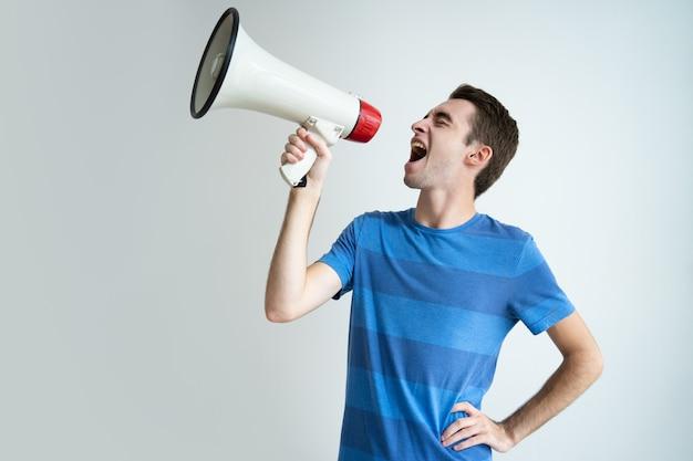 Emocionado hombre atractivo gritando en megáfono