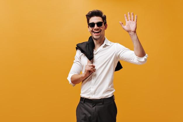 Emocionado hombre brunet encantador con camisa blanca, gafas de sol y pantalón negro sonríe, sostiene la chaqueta y saluda con la mano en la pared naranja.