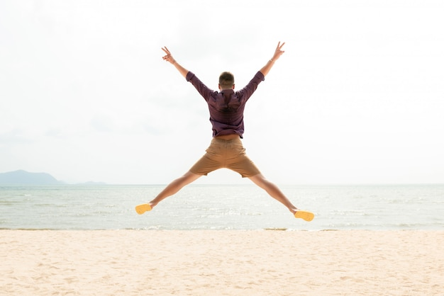 Emocionado hombre feliz enérgico saltando en la playa