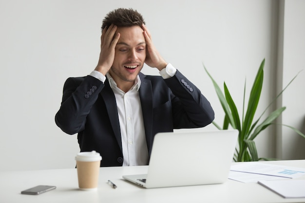 Emocionado hombre de negocios del milenio sorprendido por inesperadas buenas noticias en línea
