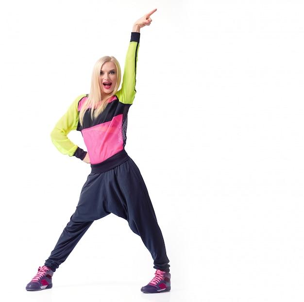 Emocionado joven activo femenino posando con su brazo en el aire vistiendo traje deportivo copyspace aislado