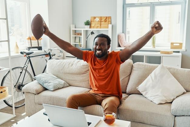 Emocionado joven africano animando y sonriendo mientras ve el partido deportivo en casa