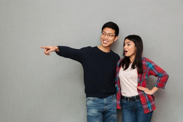Emocionado joven asiática pareja amorosa señalando.