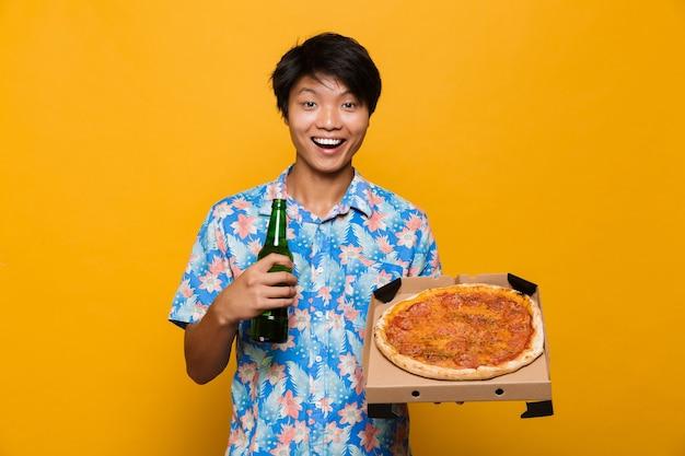 Emocionado joven asiático que se encuentran aisladas sobre un espacio amarillo sosteniendo pizza bebiendo cerveza.