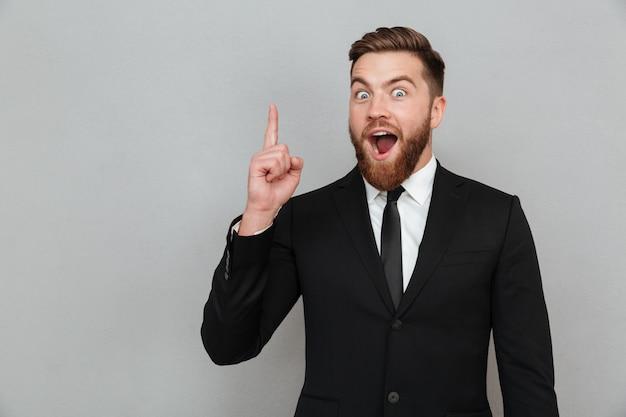 Emocionado joven empresario barbudo teniendo una idea