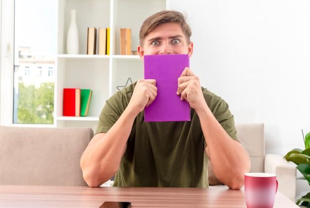 Emocionado joven guapo rubio se sienta a la mesa con la taza y el teléfono sosteniendo y mirando por encima del libro