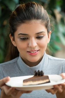 Emocionado joven mujer sosteniendo la placa con la torta