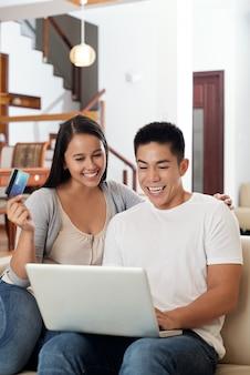 Emocionado joven pareja asiática sentada en el sofá en casa con computadora portátil y tarjeta de crédito