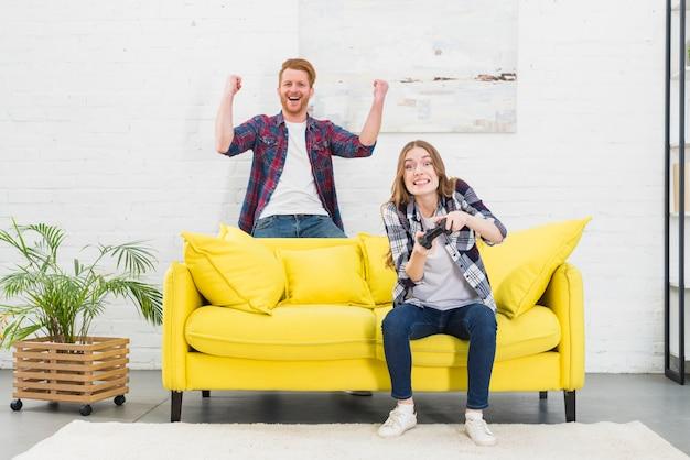 Emocionado joven pareja disfrutando jugar videojuegos en casa