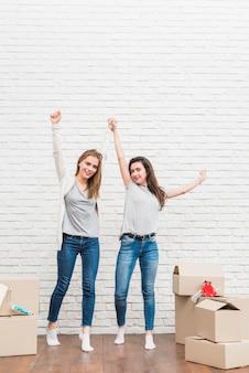 Emocionado joven pareja sosteniendo sus manos de pie contra la pared de ladrillo blanco