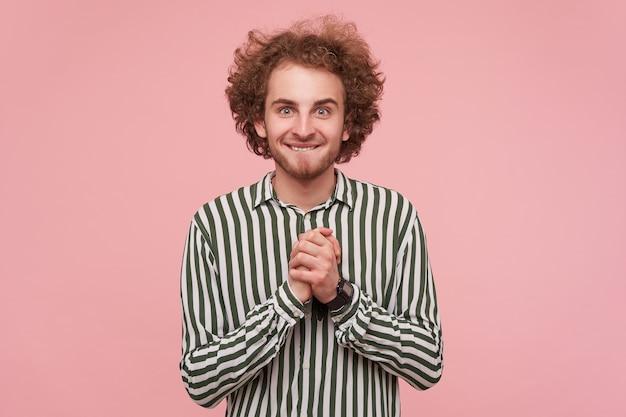 Emocionado joven pelirrojo barbudo de ojos verdes vestido con ropa casual doblando las manos levantadas y mordiendo el labio inferior mientras está parado sobre una pared rosada con camisa a rayas