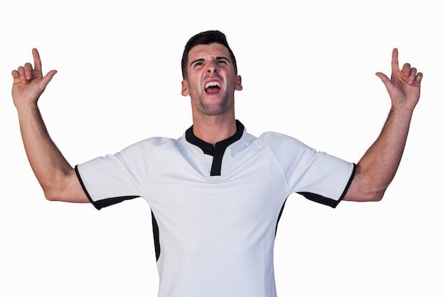 Emocionado jugador de rugby apuntando hacia arriba