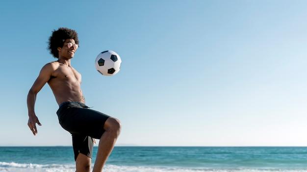 Emocionado macho negro joven golpea la pelota en la orilla del mar
