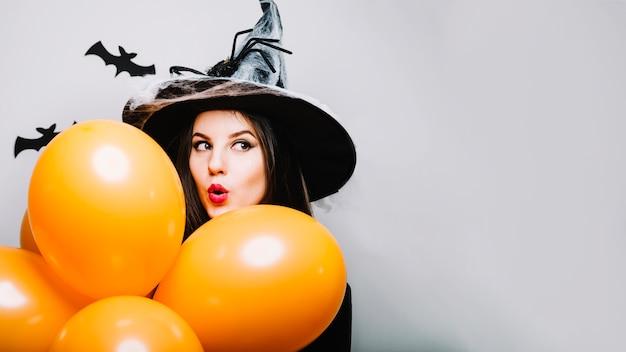 Emocionado niña bruja con globos