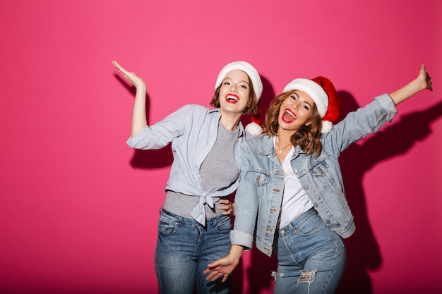 Emocionado sonriendo dos amigas con sombreros de navidad santa