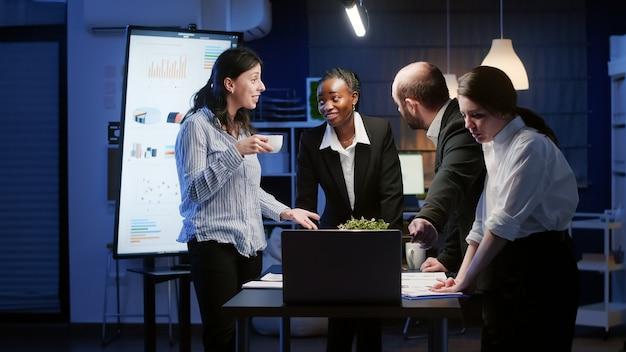 Emocionado trabajo en equipo de diversos negocios recibiendo buenas noticias aplaudiendo mientras está de pie en la mesa