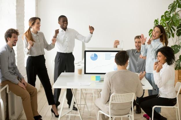 Emocionados por las buenas noticias, colegas motivados que celebran juntos el éxito corporativo.