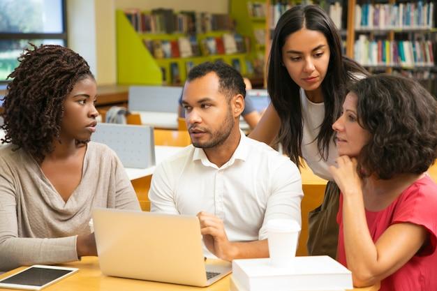 Emocionados colegas discutiendo algunas preguntas en la biblioteca