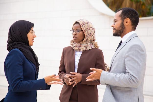 Emocionados colegas de negocios discutiendo proyectos fuera