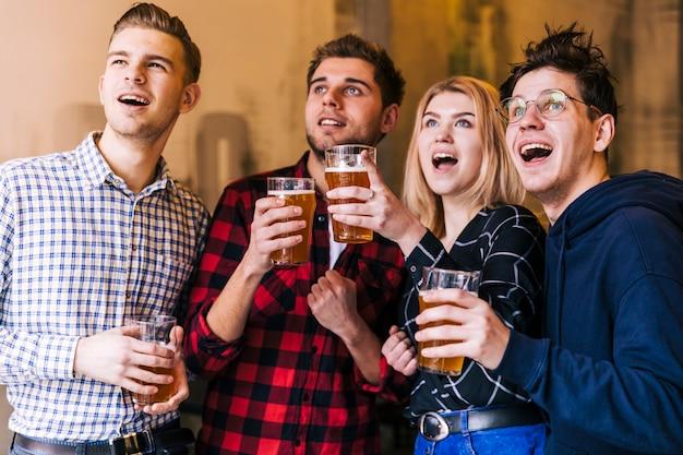 Emocionados jóvenes amigos disfrutando de la cerveza mientras miran algo.