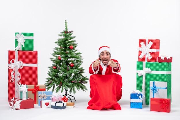Emocional emocionado joven vestido como papá noel con regalos y árbol de navidad decorado apuntando algo sobre fondo blanco.