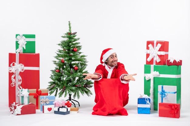 Emocional emocionado joven vestido como papá noel con regalos y árbol de navidad decorado dando la bienvenida a alguien sobre fondo blanco.