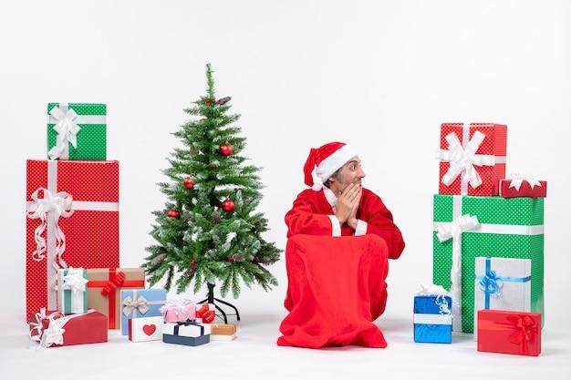 Emocional emocionado joven vestido como papá noel con regalos y árbol de navidad decorado mirando en algún lugar del lado izquierdo sobre fondo blanco.