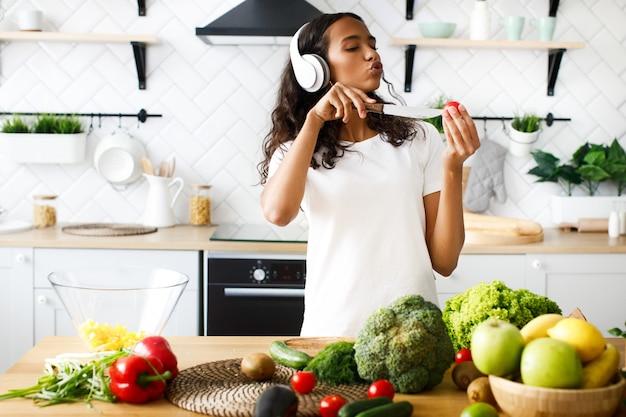 Emocional joven africana está escuchando música a través de auriculares y cantando corta un tomate cherry