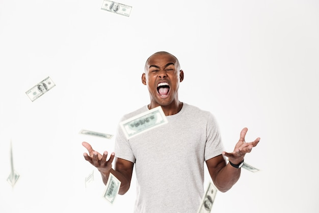 Emocional joven africano gritando con dinero.