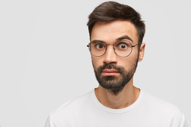Emocional joven barbudo con barba densa, peinado de moda, mira con sorpresa