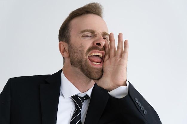 Emocional joven empresario gritando ruidosamente