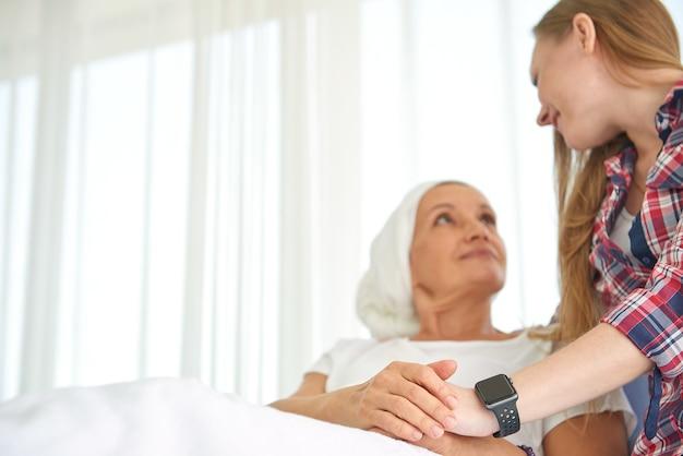 Emocional de la joven hija blanca caucásica con esperanza y sonrisa visitando y alentando a apoyar a su madre que usa pañuelo en la cabeza y lucha contra el cáncer de mama en una habitación de hospital limpia y clara
